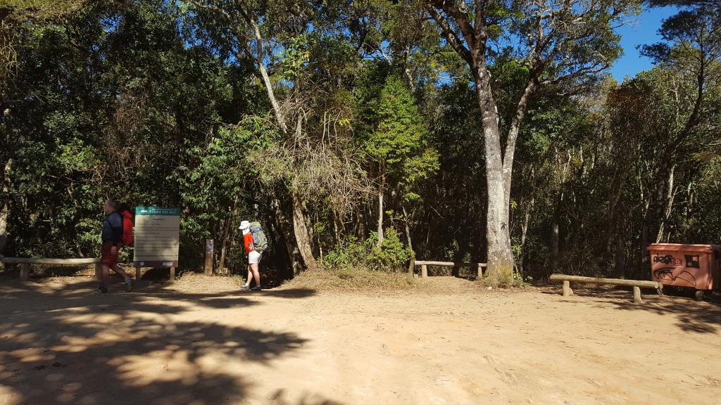 Estacionamento do Bauzinho, na frente da Michelle tem a trilha principal que vai direto ao cume do Bauzinho, a direita na altura do lixo tem uma trilha menor que leva a base das vias.